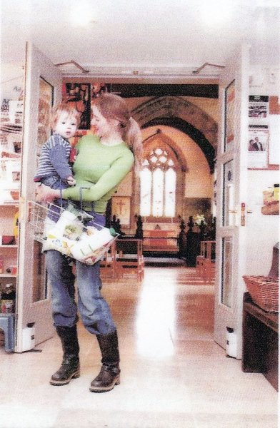 A customer holding ner child in the doorway with the church behind
